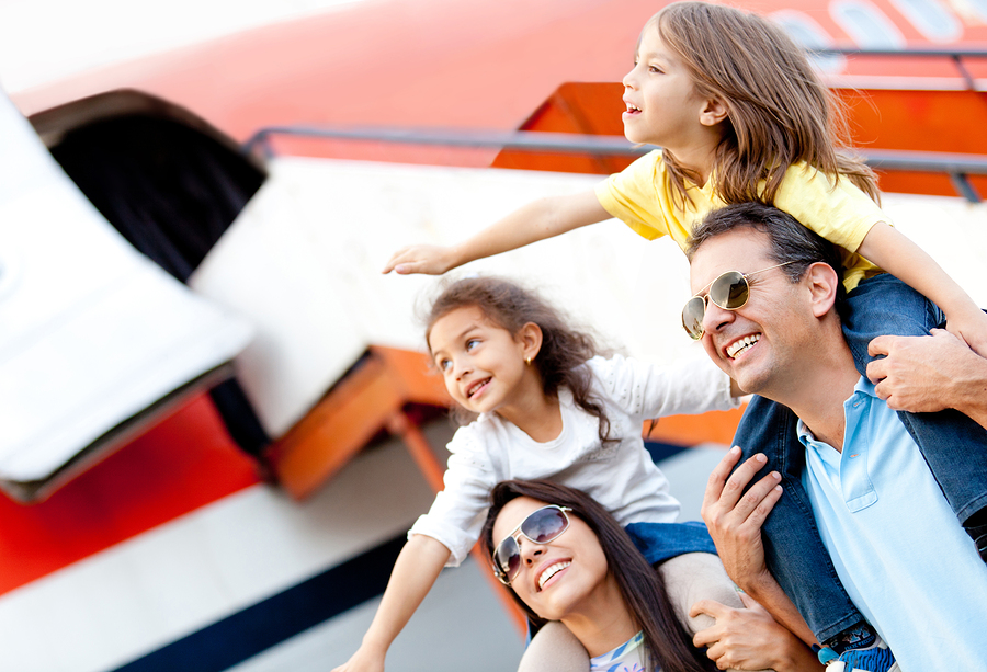 Excited family standing by plane