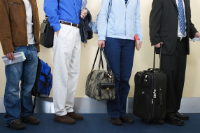 Passengers with hand luggage waiting to board their plane