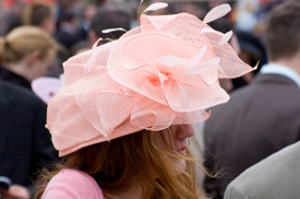 Wearing a feathered hat at a horse racing event